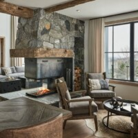 rustic modern family room with stone fireplace and wood beams